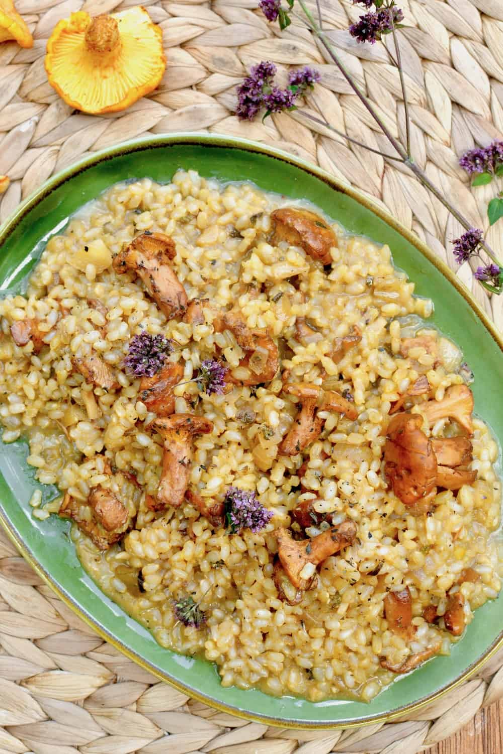 The golden yellow colour of the risotto with wild chanterelle mushrooms and purple oregano flowers