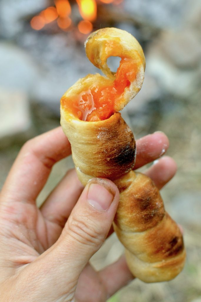 A stickbread with the hole filled with apricot jam