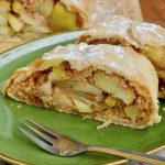 Two pieces of apple strudel and a fork on a plate, showing the cooked apple filling and a crispy crust.
