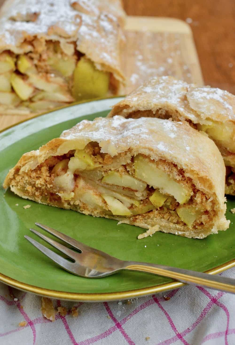 A slice of baked apple strudel, showing the filling of apples and breadcrumbs and a crisp crust.