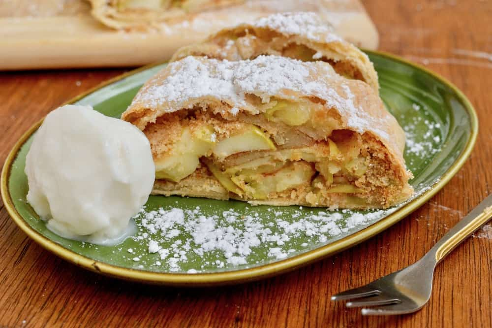 A slice of apple strudel topped with icing sugar, on a plate with a scoop of vanilla ice cream.