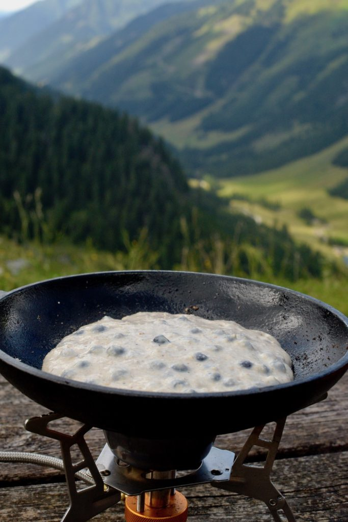 Cooking a blueberry pancake on a camping stove