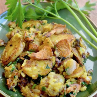 A plate of fried potatoes, wild mushrooms, and vegan egg garnished with parsley