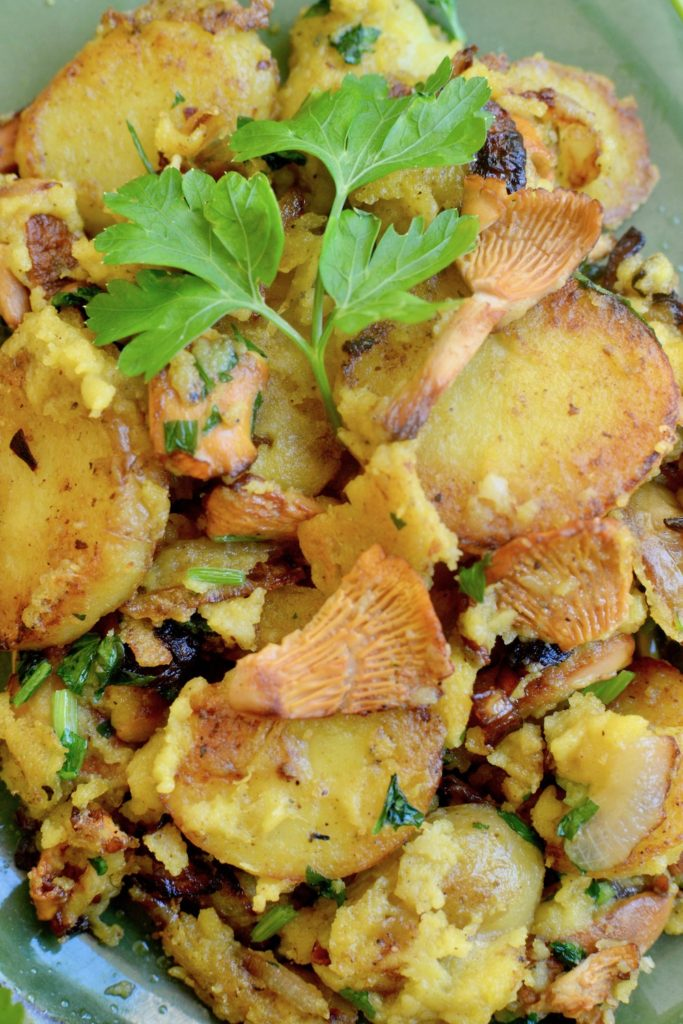 Golden yellow potatoes and chanterelle mushrooms scrambled together.