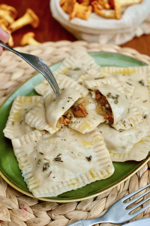 A cut open ravioli reveals the delicious mushroom filling