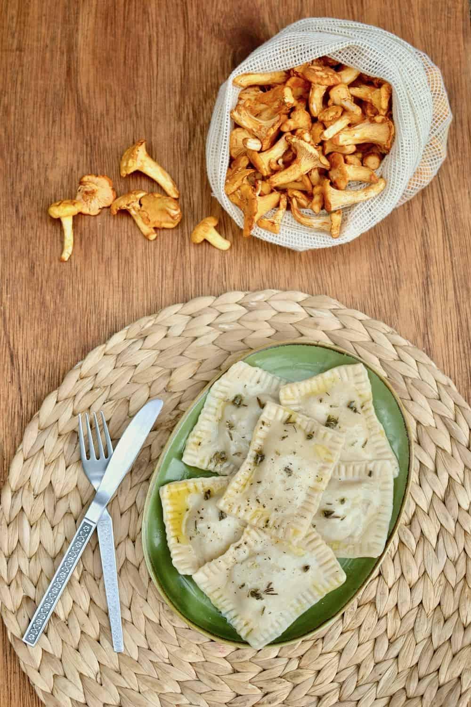 A bag of wild chanterelle mushrooms alongside a plate of ravioli
