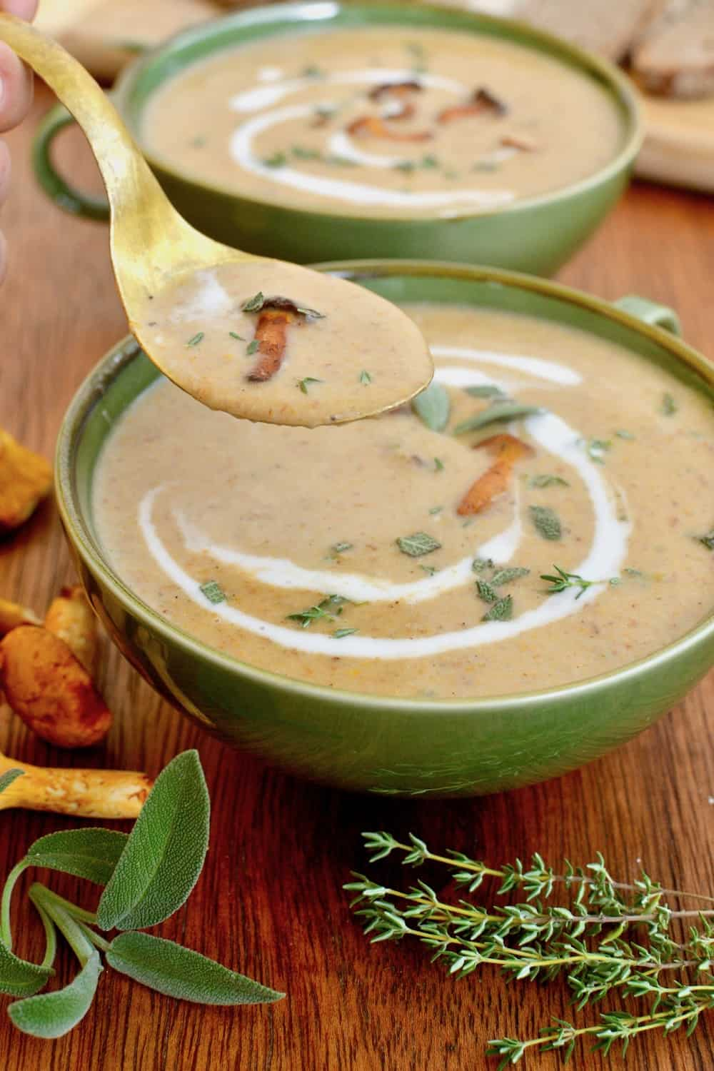 A spoonful of creamy chanterelle soup with a small, whole mushroom on top is lifted from a bowl of soup, around which are lying some fresh herbs.