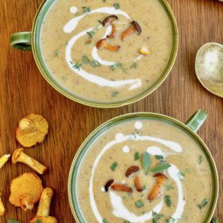 Two bowls of chanterelle soup decorated with a swirl of coconut cream and fresh herbs