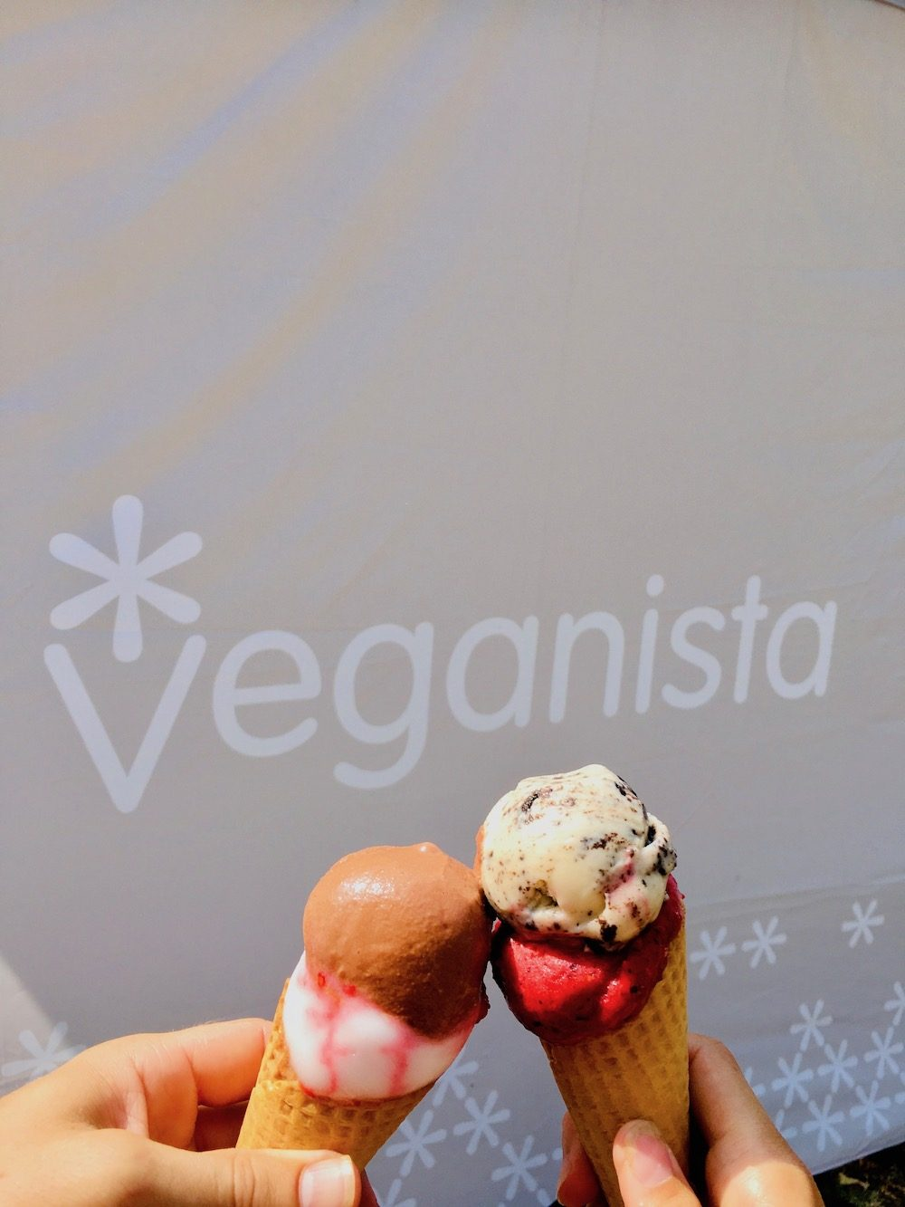 Two cones of ice cream in front of a Veganista banner