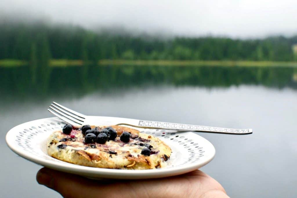 The wild blueberry pancake comes into focus with a blurred landscape behind it.