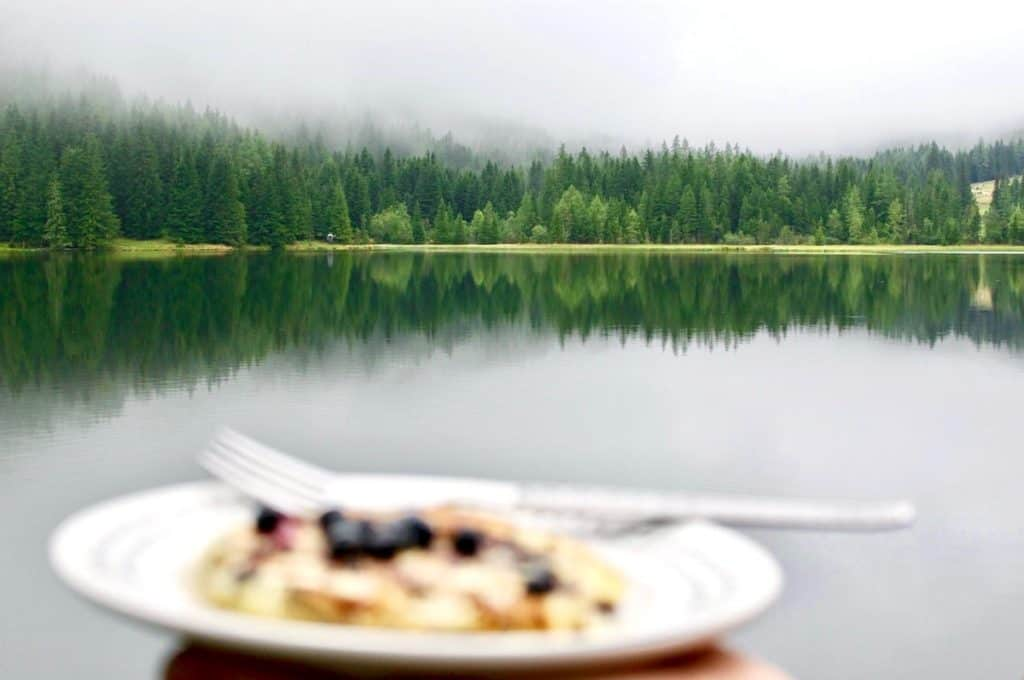 Pine trees and their reflection in a lake, with an out of focus pancake in the foreground