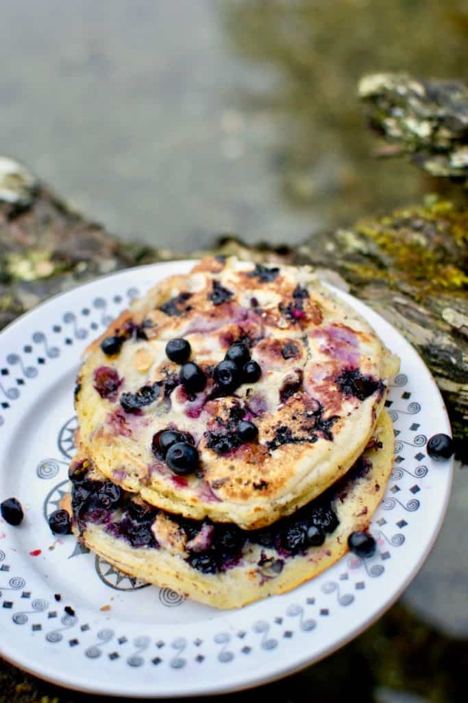 Wild blueberry pancakes topped with extra berries and a sprinkle of brown sugar