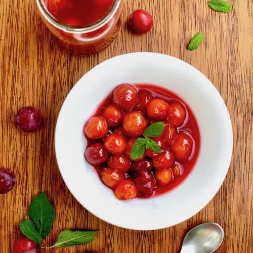A white bowl with red plum compote garnished with mint