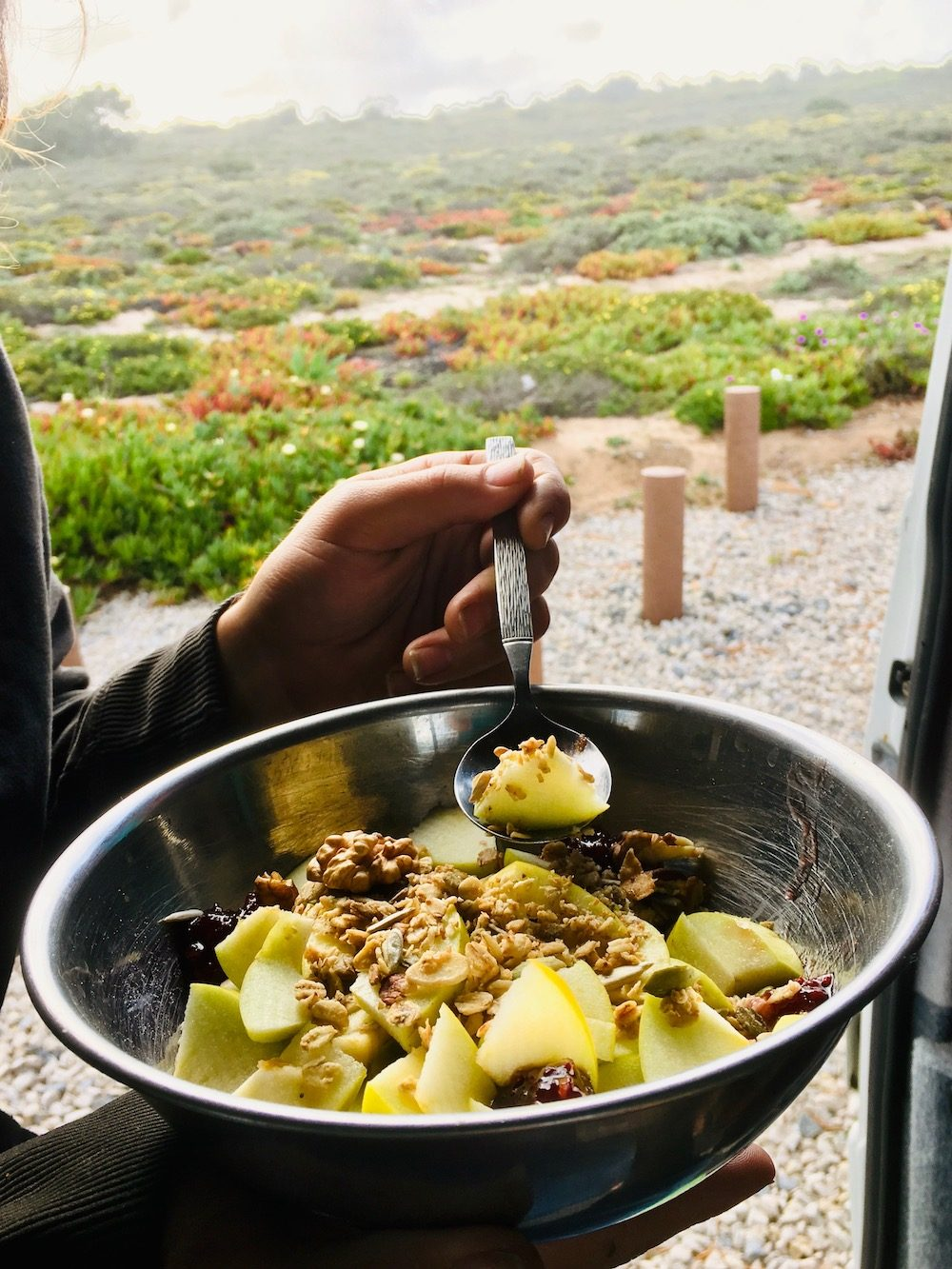 Enjoying a bowl of apple and cranberry porridge when camping in Portugal