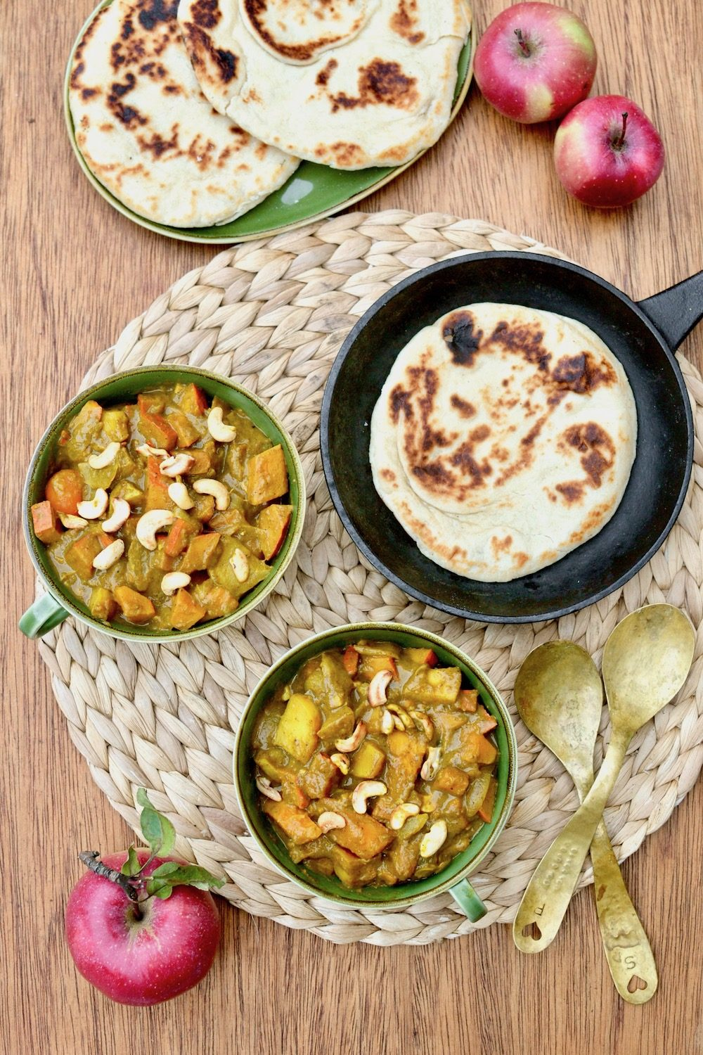Two bowls of vegan pumpkin curry on a wooden board alongside apples and naan bread.