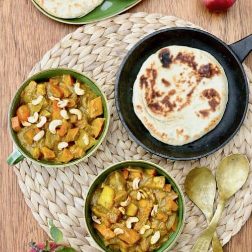 Two bowls of pumkin curry on a wooden board next to naan bread and apples