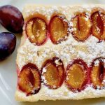 A piece of light vegan sponge cake with plums and icing sugar on top.
