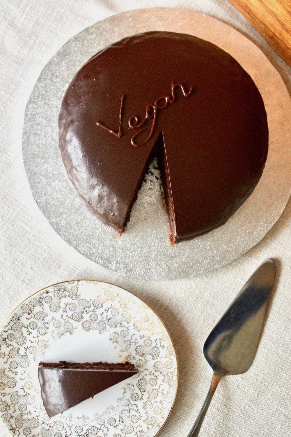 "A sachertorte covered in dark chocolate glaze, with ""Vegan"" written on top"