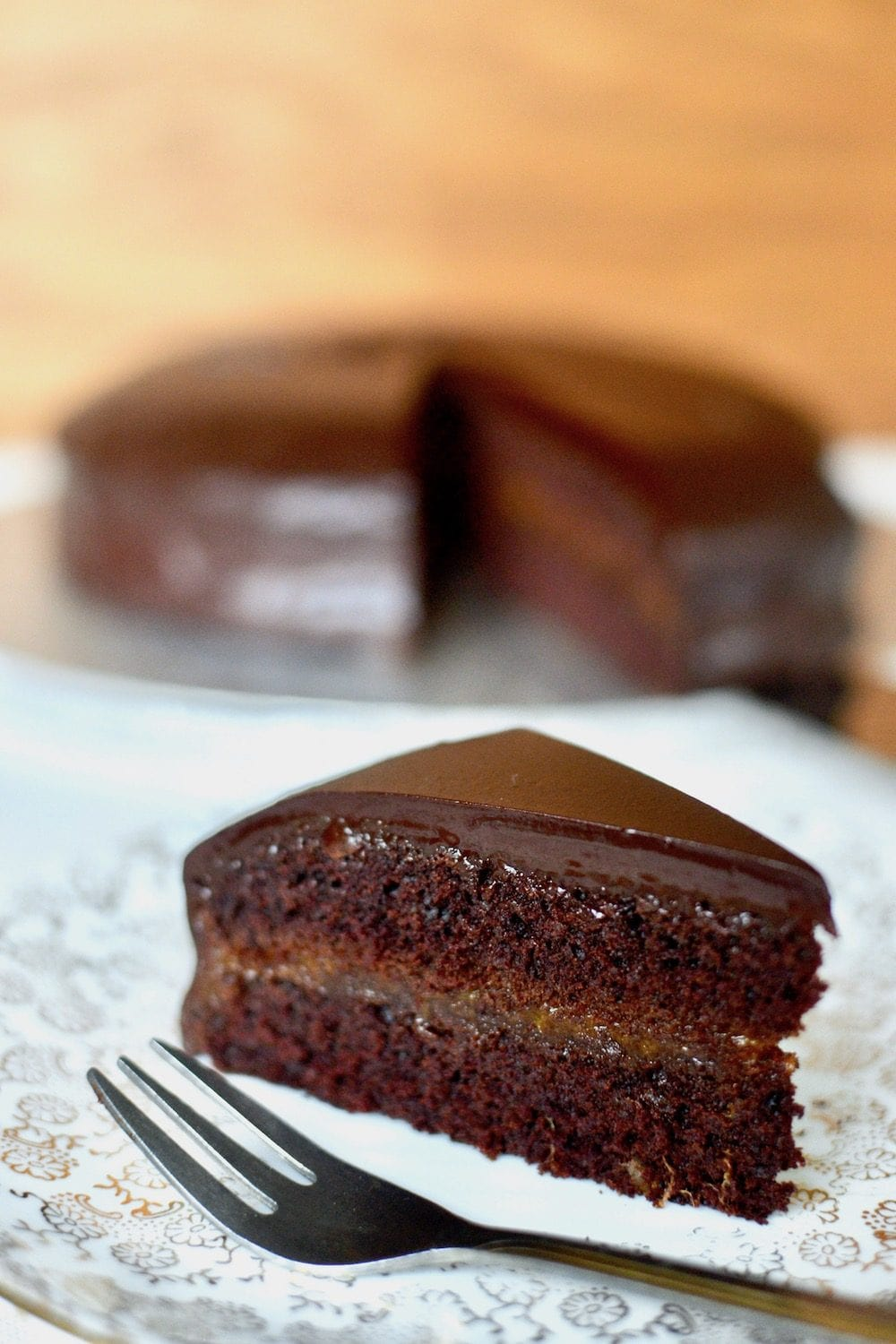 A slice of vegan sachertorte on a plate. The rest of the chocolate cake can be seen in the background.