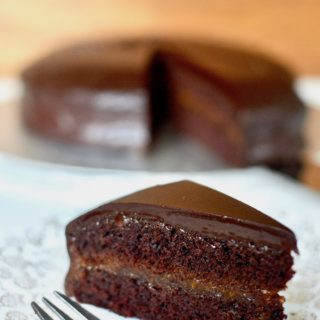 A slice of sachertorte on a plate, with the remaing chocolate cake behind