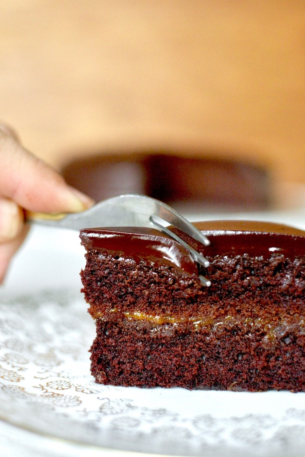 A cake fork cuts through the dark chocolate glaze of the vegan sachertorte