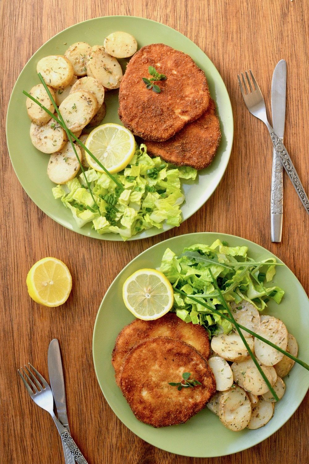 Two plates with salad and golden brown schnitzel ready to eat.