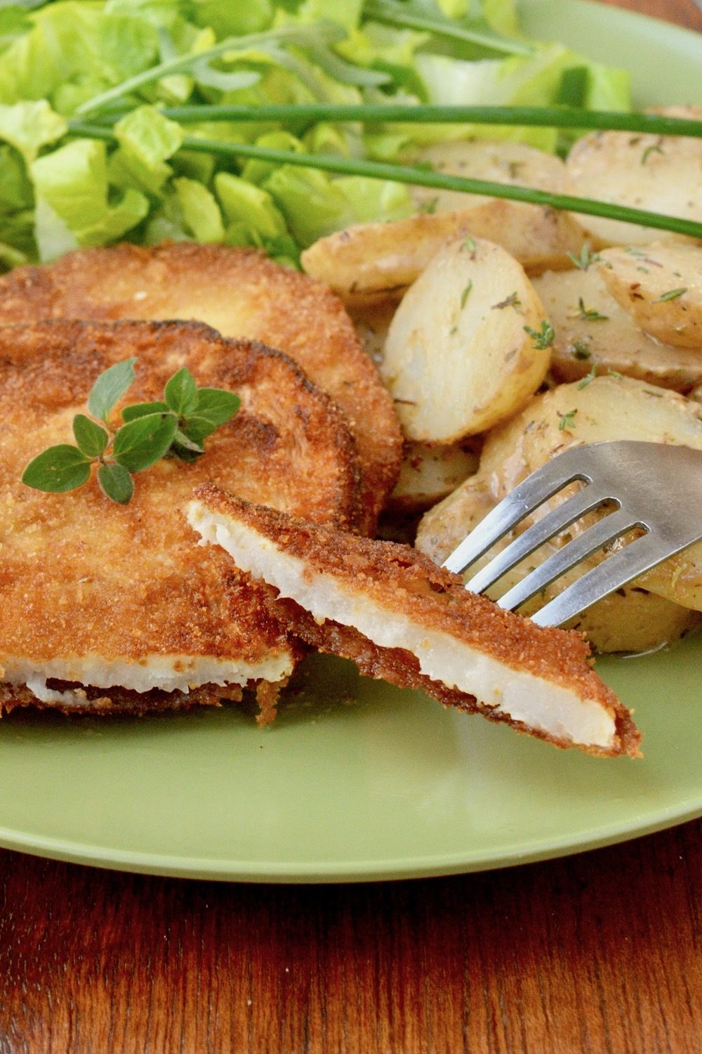A slice of schnitzel reveals the tender, white inside.