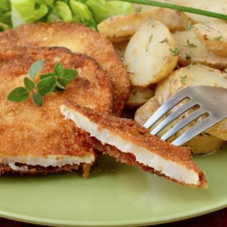 a bite of celeriac schnitzel on a fork is lifted from a plate of schnitzel and potato salad..