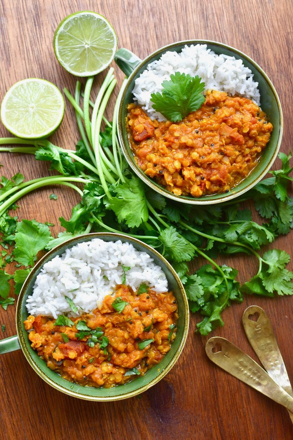 Two bowls of red lentil dal served with rice and fresh coriander