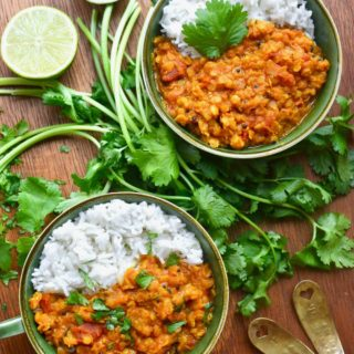 Two green bowls filled with red lentil dal, white rice and garnished with coriander leaves