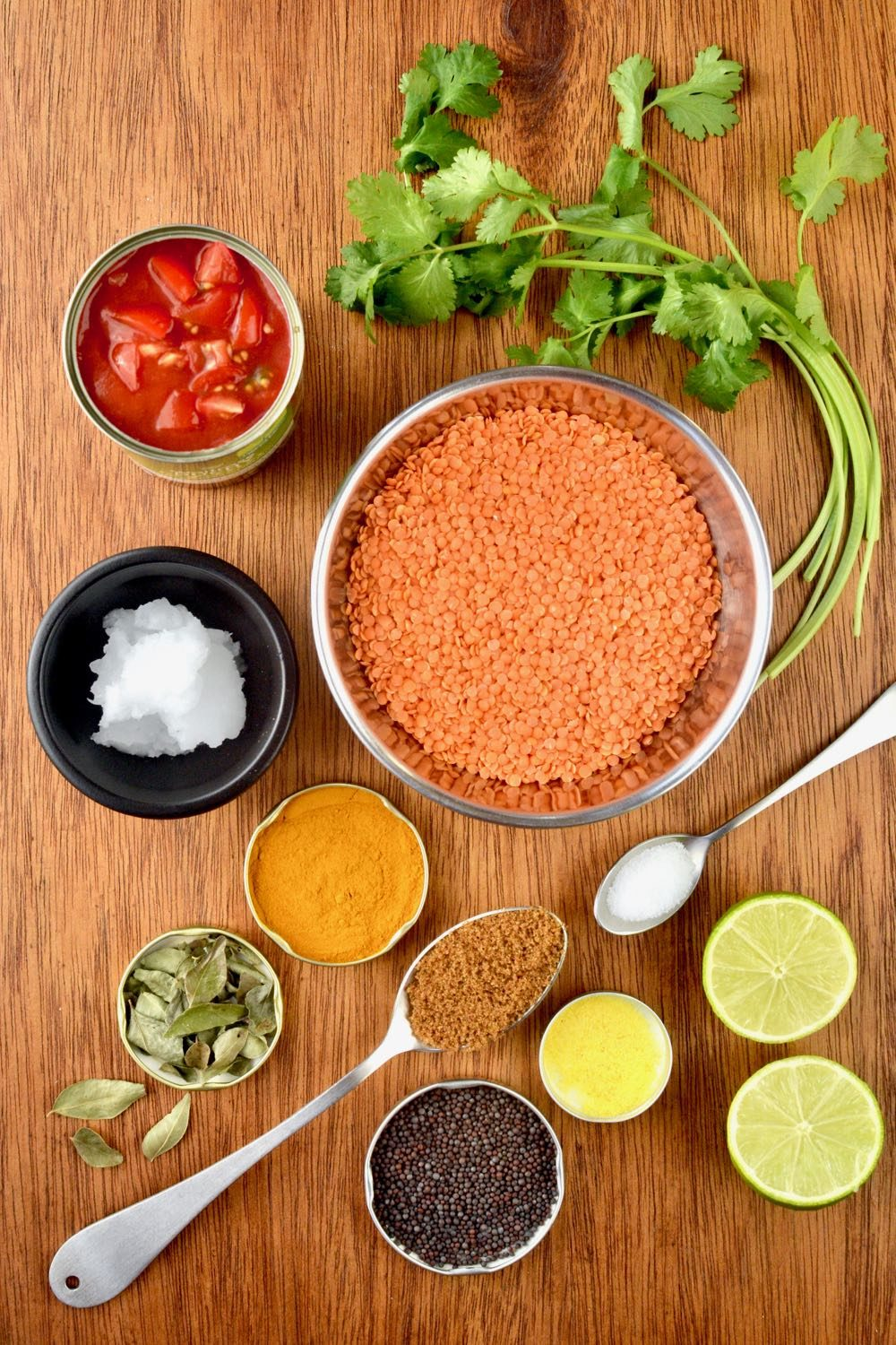 All the ingredients you need for this vegan red lentil dahl - lentils, spices, coconut oil, coriander, lime and tomatoes