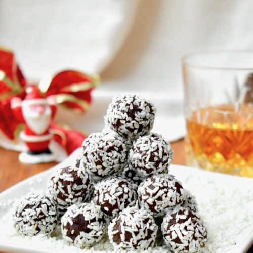 Coconut covered chocolate truffles stacked in a pyramid