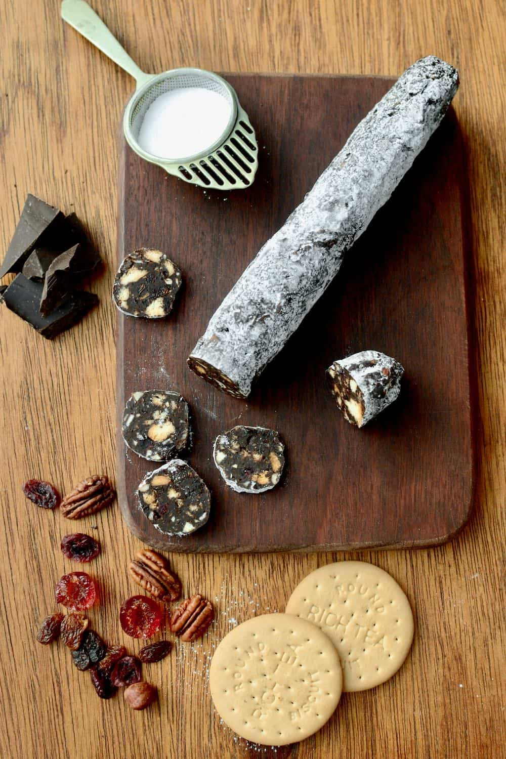 A vegan chocolate salami on a board, surrounded by its ingredients - chocolate, fruit, nuts and biscuits.