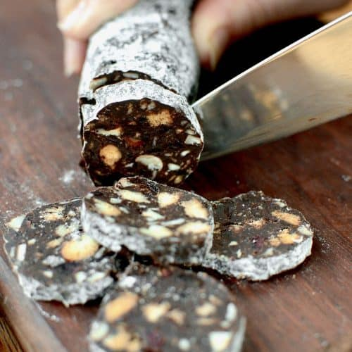A knife cuts into a chocolate salami filled with biscuits and nuts