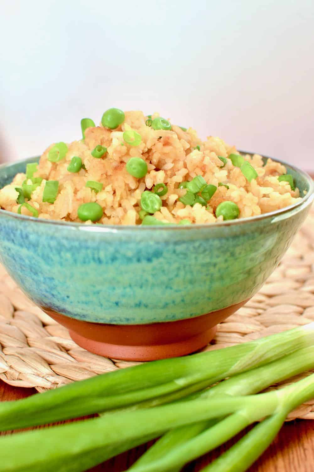 A bowl of vegan egg fried rice with peas and spring onions