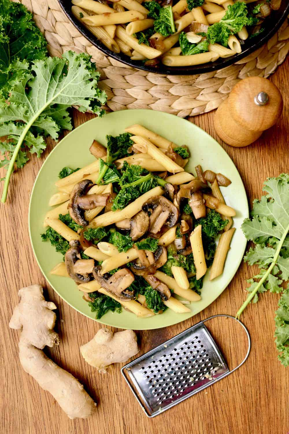 A plate of pasta, with a fresh ginger and kale around it.