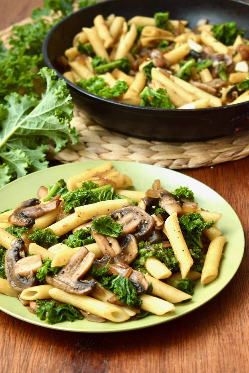 A plate of pasta with mushrooms and stirfried kale