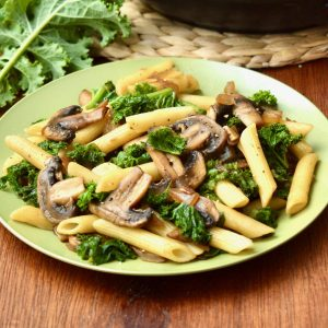 A plate of penne pasta with kale and mushrooms