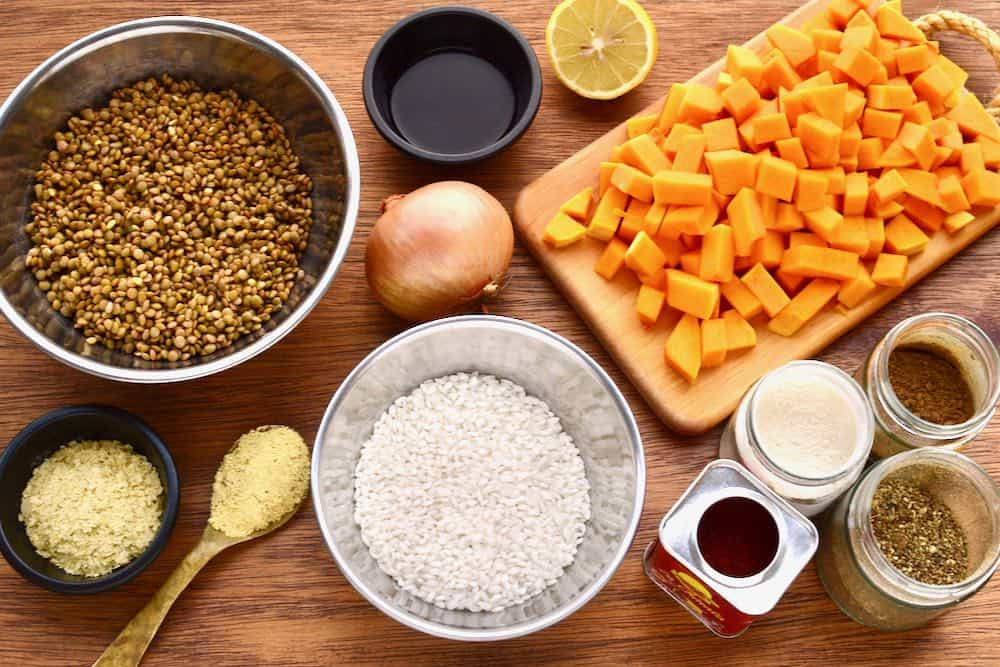 The ingredients for lentil risotto are laid out on a worktop - lentils, arborio rice,  squash, onion and spices.