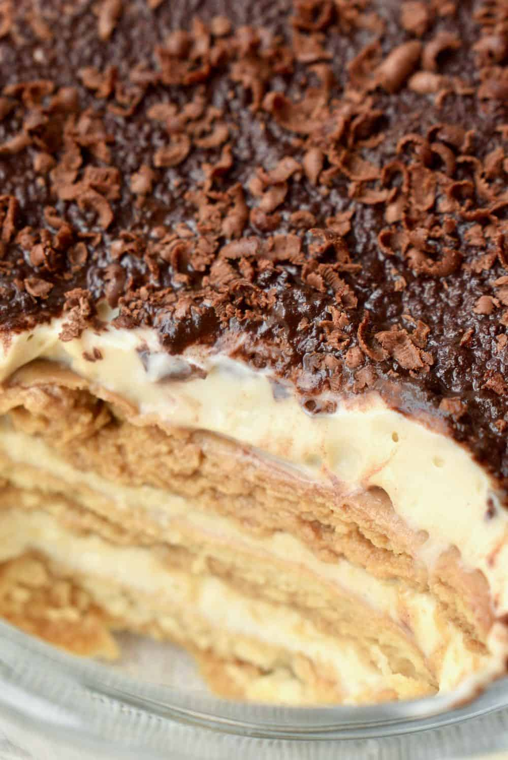 A close up shows the rich creamy layer, the coffee soaked biscuits and dark chocolate topping