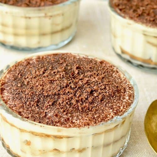 A chocolate covered vegan tiramisu in a glass ramekin