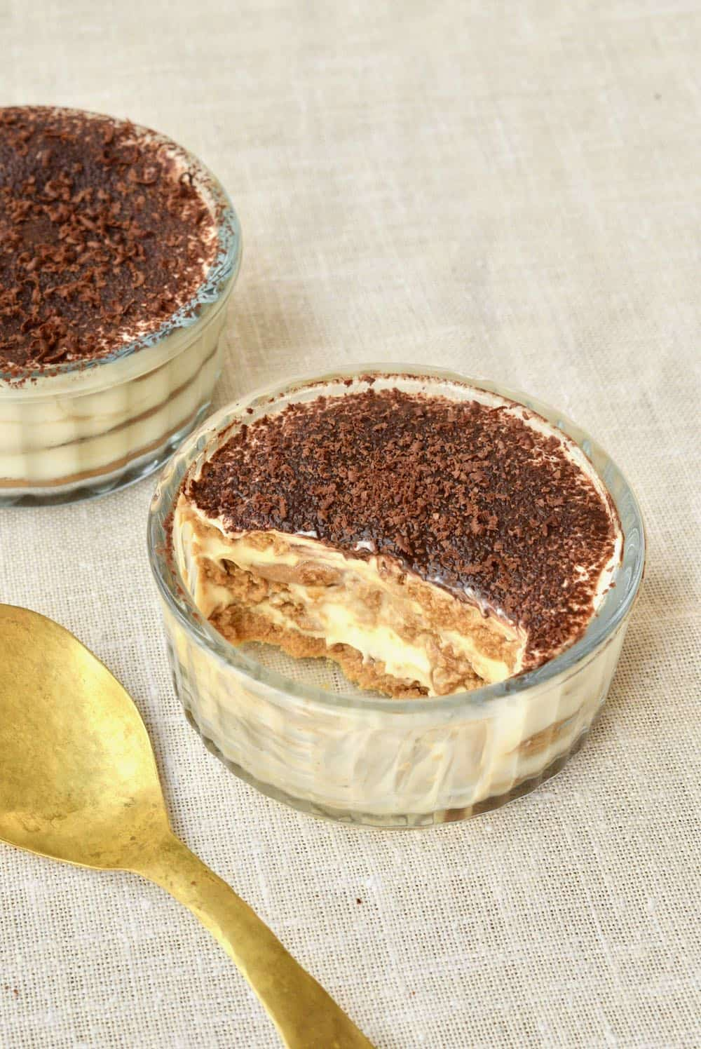 A serving of vegan tiramisu in a glass ramekin, revealing the layers inside.