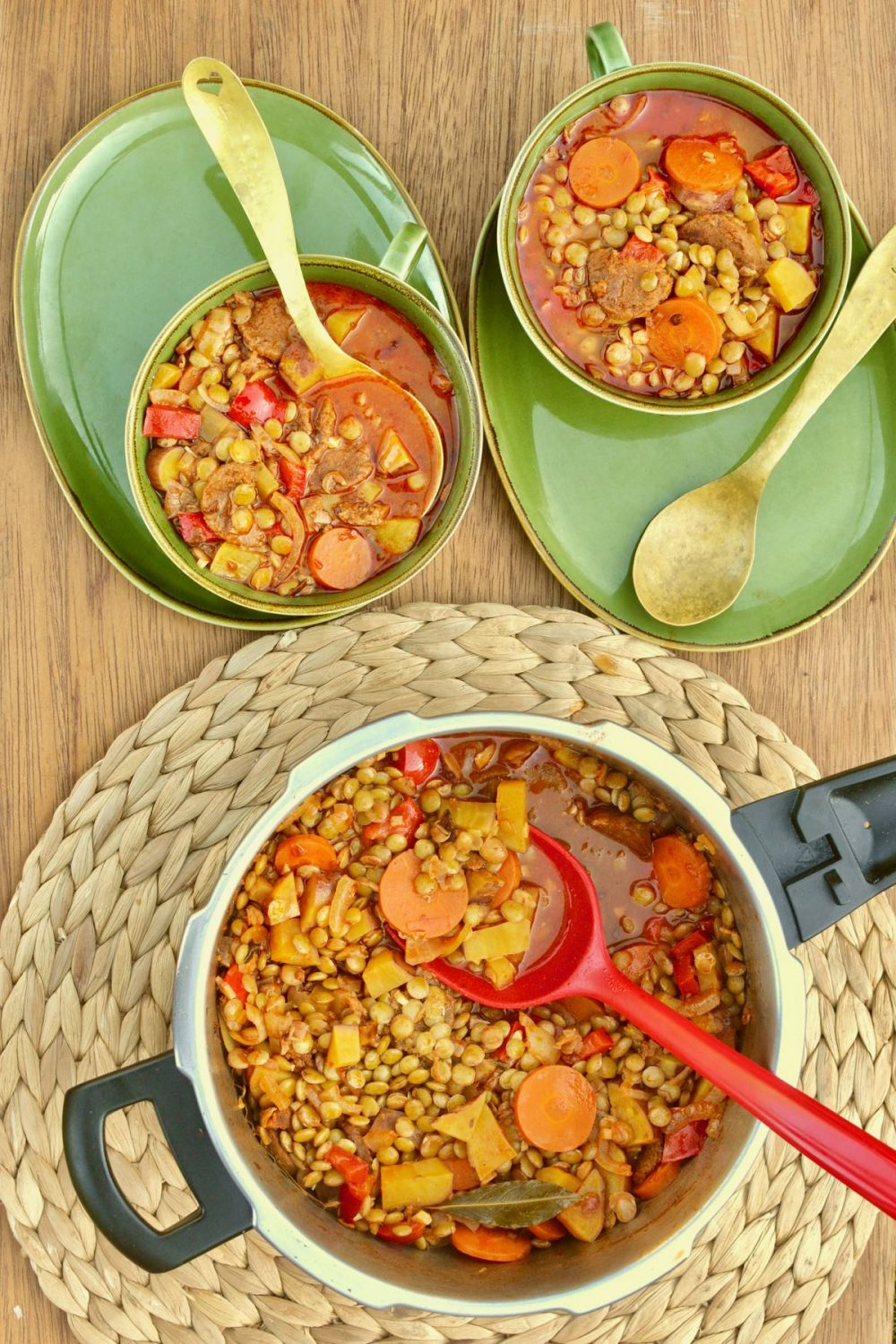 Two green bowls full of rich red coloured vegan lentil stew
