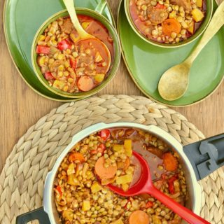 A pressure cooker full of lentil stew with a red ladle, and two bowls of stew ready to eat