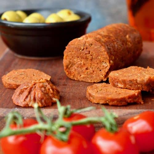 A sliced vegan chorizo on a wooden board, next to tomatoes and olives