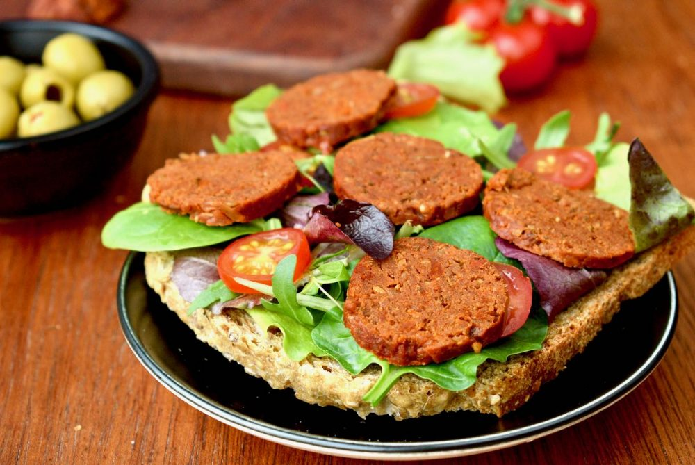 A slice of bread topped with green salad, tomatoes and vegan chorizo slices