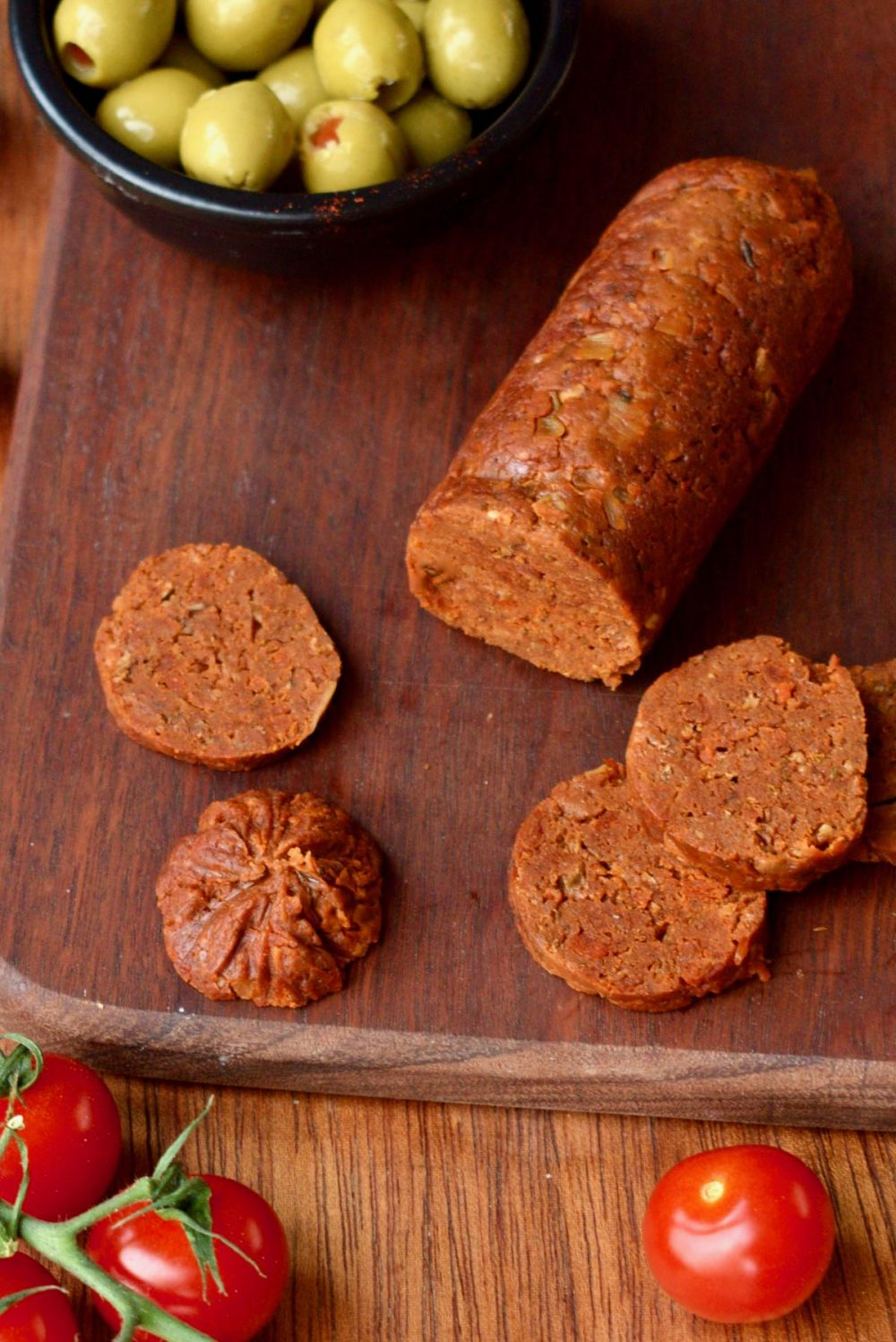 A dark wooden board with slices of vgean chorizo on. The chorizo is a rich orange colour.