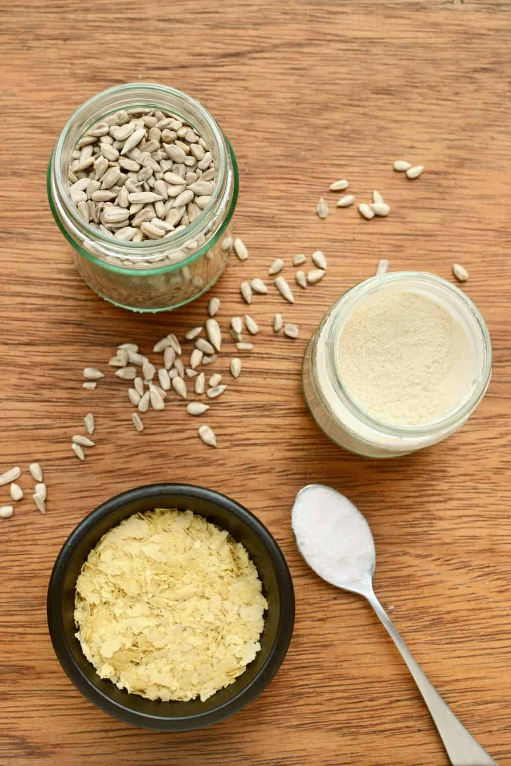 All the ingredinet laid out on a board - sunflower seeds in a jar, nutritional yeast flakes, garlic powder and salt