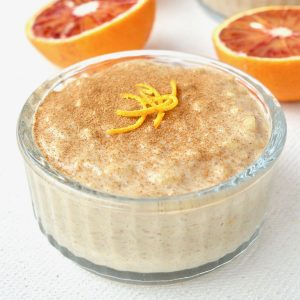 A glass ramekin of rice pudding, topped with cinnamon and orange zest