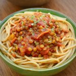 Lentils in a rich red tomato sauce on top of a bowl of spaghetti